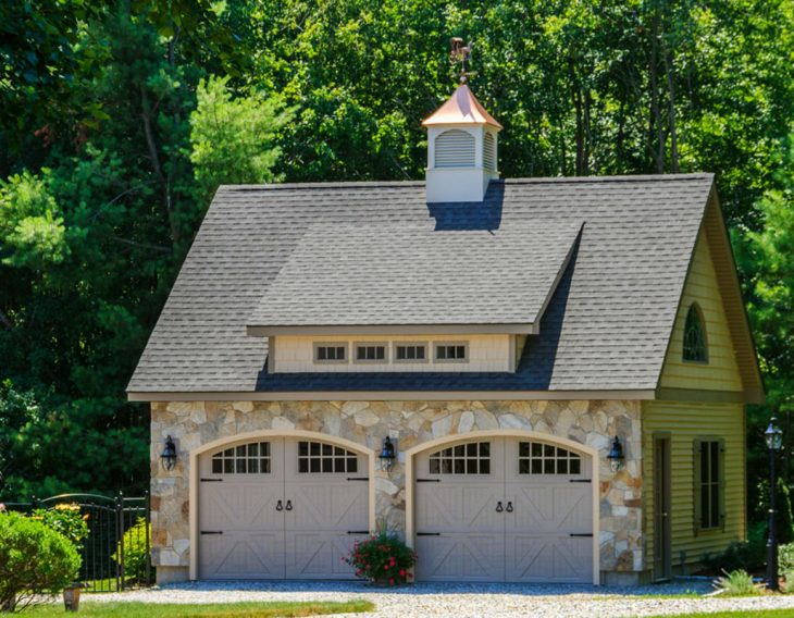 small detached custom garage with stone siding