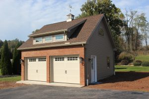 side view of brick two car garage with cupola on top