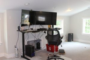 standing desk and chair set up in garage with home office